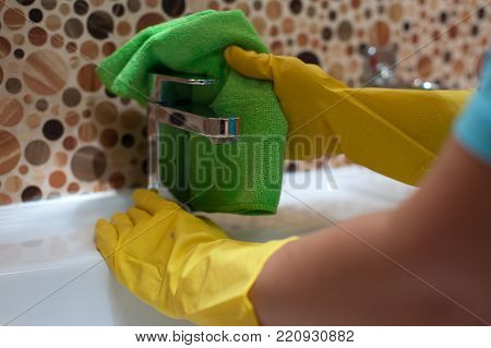 Closeup of female employee of cleaning company doing cleaning in the bathroom and wiping sink with rag