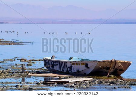January 2, 2018 in Bombay Beach, CA:  Abandoned paddle row boat rental on a forgotten beach at the shrinking Salton Sea caused by drought conditions taken in Bombay Beach, CA where people can see how a once vibrant beach community turned into a ghost town