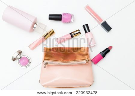 Cosmetics and cosmetic bag of pink color on a white background. Flat lay