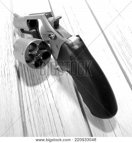 A stainless steel unloaded revolver on a wooden table with it's cylinder opened showing it's opened.