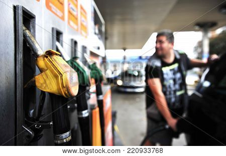 Man holding Gasoline pistol at gas station