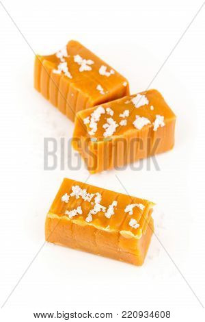 Hand made caramel toffee pieces with sea salt over white background