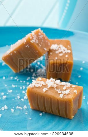 Hand made caramel toffee pieces with sea salt on blue plate on kitchen table