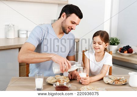 Happy father and daughter have breakfast at kitchen, eats delicious pancakes with jam, drink milk, enjoys delicious food prepared by mother. Family apetizes yummy sweet dish. Eating and people concept