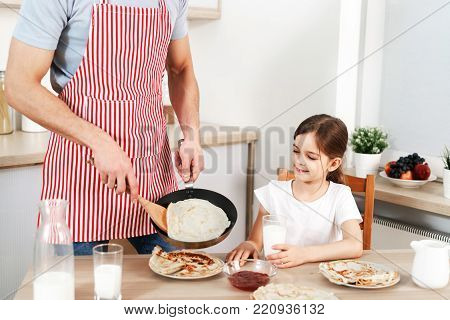 Cropped shot of man in apron involved in cooking, fries delicious pancakes for his daughter, preapres breakfast, brings up child. Cheerful kid drinks milk with flannel cake. Family breakfast