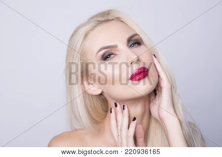 Perfect woman's skin condition. Blonde woman over 30 with red lips and blue eyes touching her face.