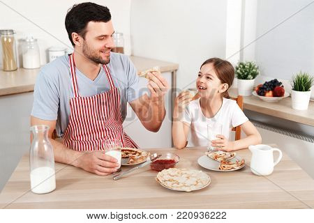 Cheerful handsome young male and little child eat pancakes together, drinks fresh milk, enjoy breakfast at kitchen, being in good mood, going to have walk in park. Family and childhood concept