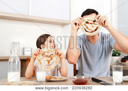 Glad positive young father foolishes with her small daughter at kitchen, make faces from pancakes, have tasty breakfast, pose at camera, drink fresh milk, eat flannel cakes with sweet jam