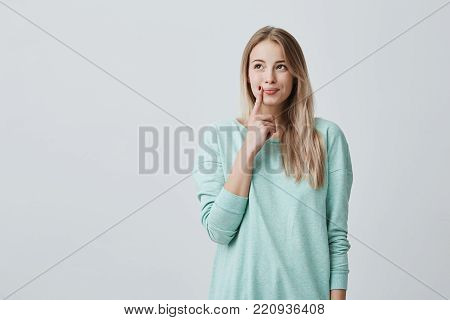 Caucasian female model with long blonde hair dressed casually looks aside with dreamful expression, builds plans for future, has cunning expression of face. Emotions and face expression concept