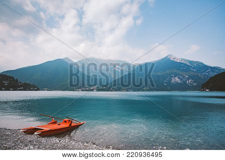 Italy view of a mountain lake lago di ledro with a beach and a lifeboat catamaran of red color in summer in cloudy weather.