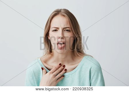 Dissatisfied blonde female model frowns face, has disgusting expression, shows tongue, expresses non-compliance, irritated with somebody, rejects do something. People and negative facial expressions