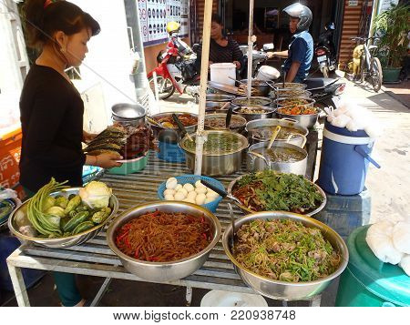 Siem Reap, Cambodia - May 03, 2013: Woman selling food in the famous pub street in the center of Siem Reap on May 03, 2013