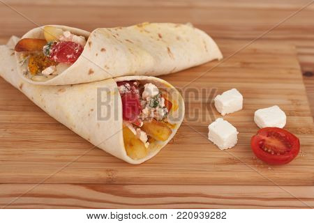 Tortilla wraps with chicken meat, tomato, french fries and feta cheese, traditional greek fast food called souvlaki or gyros in pita.