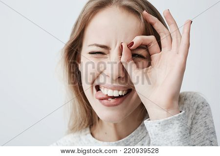 Close up isolated shot of young positive woman with long fair hair looking at camera through ok-gesture, biting her tongue in excitement. Beautiful blonde female with dark eyes has playful good mood.