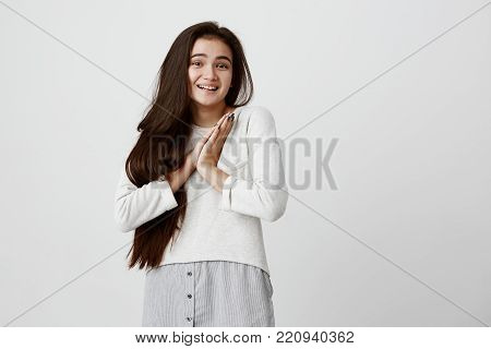 Beautiful young female with dark eyes and healthy skin having surprised and excited expression keeping her hands together smiling broadly. Happy glad girl with long dark hair expressing positive emotions poster