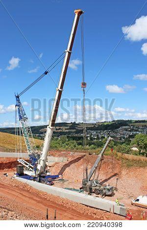 mobile crane lifting a concrete bridge beam
