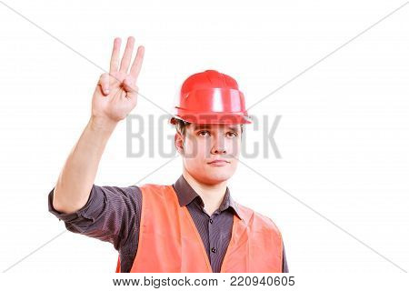 Job and work concept. Young male worker in safety vest and hard hat holding hand up showing three fingers. Repairman inspector at work.