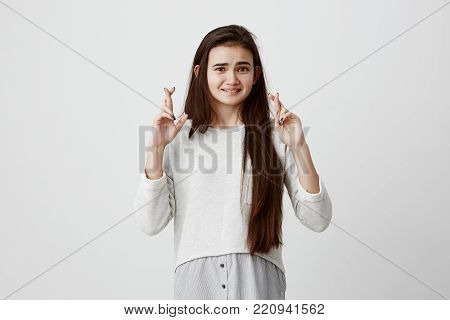 Body language. Superstitious teenager girl with dark straight hair and pretty face, clenching teeth, crossing fingers for good luck, hoping her wishes will come true, having excited look. Human emotions and feelings