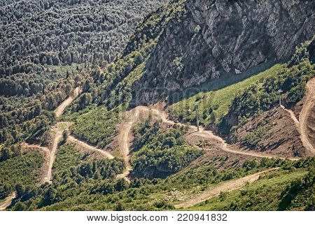 Mountain landscape  steep mountains, covered with forests, form a deep gorge, on the slope of a mountain winding road with steep turns - a mountain serpentine.