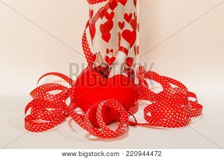 A message in the bottle with harts on it and a red ribbon around it and red hart
