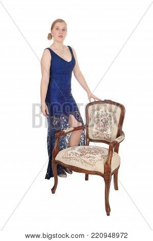 A beautiful young woman standing in a blue long evening gown with an old antique armchair, isolated for white background