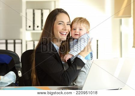 Portrait of a happy working mother posing with her baby and looking at camera at office
