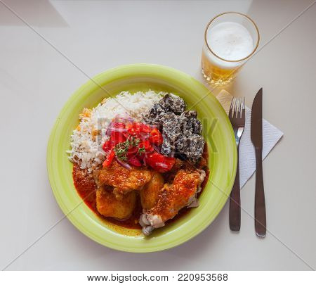 Typical Bolivian food. stewed chicken stuffed with spicy sauce served with steam rice, dried potatoes and salad with tomatoes and onions. stock photo