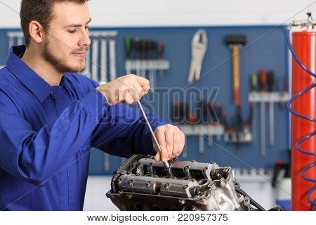 Satisfied mechanic repairing a motorbike engine in a mechanical workshop