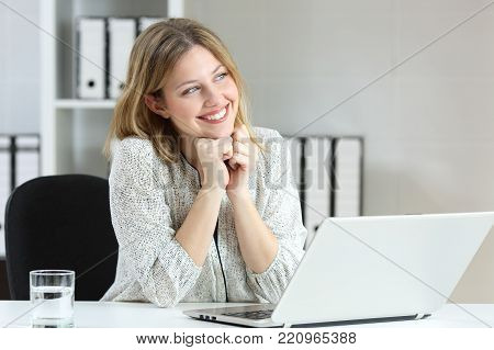 Portrait of an office worker dreaming and looking at side sitting in a desktop at workplace