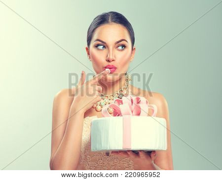 Beauty fashion model girl holding Beautiful Big Cake and tasting it. Funny joyful styled woman with wedding, party or birthday cake on green background. Diet, dieting concept. Slimming, weight loss