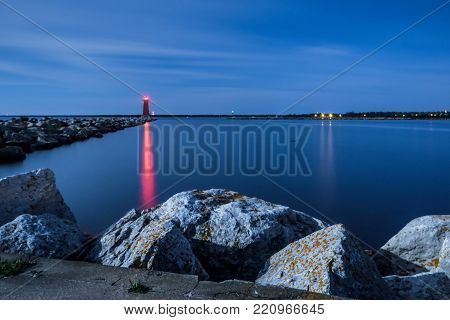 Lighthouse Beacon At Night. The guiding red light of the Manistique Lighthouse reflects on the calm blue water of a scenic Great Lakes Harbor in the Upper Peninsula of Michigan.