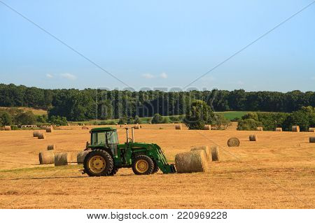 Roscoe, Missouri 7/23/2017 John Deere Tractor in a hayfield ready to lift a bale of hay.  Hay is used to feed to livestock.