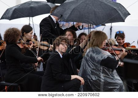 ST. PETERSBURG, RUSSIA - JULY 12, 2017: Symphony orchestra of the theater Music Hall performs outdoors under the rain during the festival All Together Opera. It was first of 4 performances