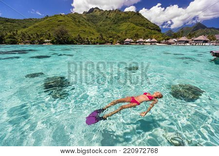 Luxury paradise travel vacation bikini woman relaxing snorkeling in idyllic ocean coral reefs at luxury overwater bungalows resort in Tahiti. French polynesia cruise lifestyle. Holiday girl getaway.