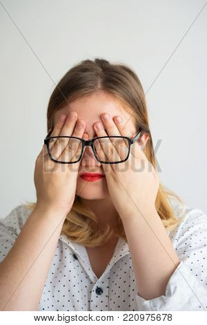 Funny woman covering eyes with hands behind glasses hiding from problems. Unhappy businesswoman crying after failure. Humor concept