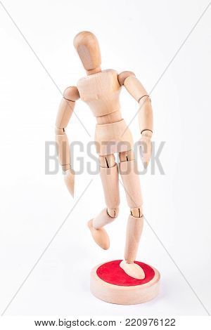 Action of wooden dummy on white background. Wooden human figurine standing on red stand over white background. Wooden human dummy is sportsman. Running wooden dummy.