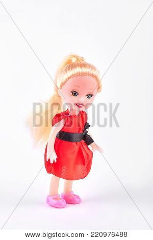 Smiling baby doll on white background. Little doll with beautiful smile in red dress standing on white background. Cute doll with positive emotions.