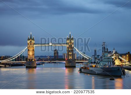 London cityscape with illuminated Tower Bridge over the River Thames and HMS Belfast at evening
