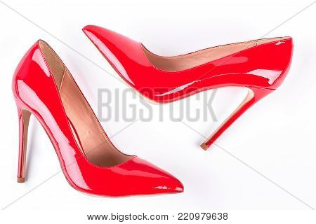 Woman red lacquered shoes on heels. Female elegant footwear on high heels over white background. Lady trendy accessories.