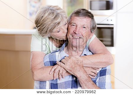 senior beautiful middle age couple around 70 years old smiling happy together at home kitchen looking sweet woman kissing husband sweetly in lifetime love concept