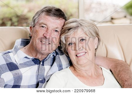 senior beautiful middle age couple around 70 years old smiling happy together at home living room sofa couch looking sweet in lifetime husband and wife enjoying life and love concept
