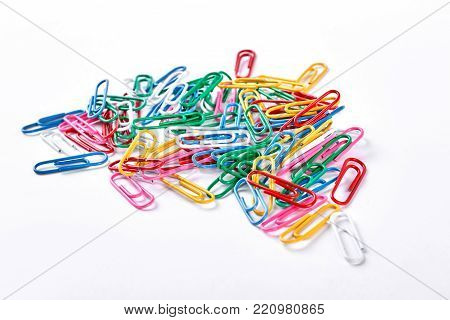 Heap of colorful plastic paper clips. Many multicolored paper clips isolated on white background.