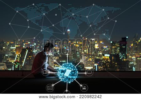 Asian businessman sitting and using the laptop for online shopping with omni channel over the cityscape background at night time, Business success and technology concept, 3D illustration
