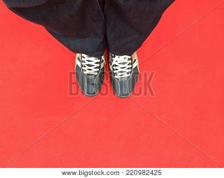 Close up of legs of a man wearing denim and black shoes standing on red carpet. View from above.