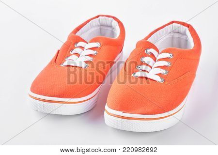 Orange vans on white background. Female colorful gumshoes isolated on white. Woman sport shoes on sale.