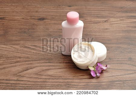 A tub of hand lotion displayed with a small pink bottle of lotion with a small purple flower
