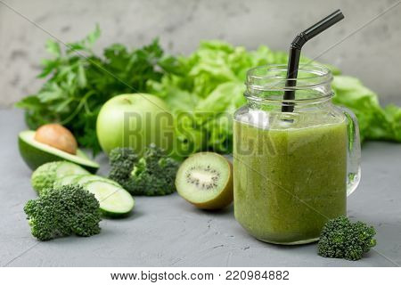 green smoothies in glass jar mason with fresh vegetables and herbs: broccoli, avocado, lime, celery, apple, kiwi, parsley. detox smoothies