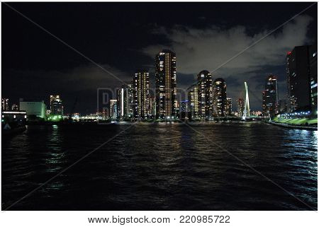 Tokyo skyscrapers at night reflected in a Sumida river