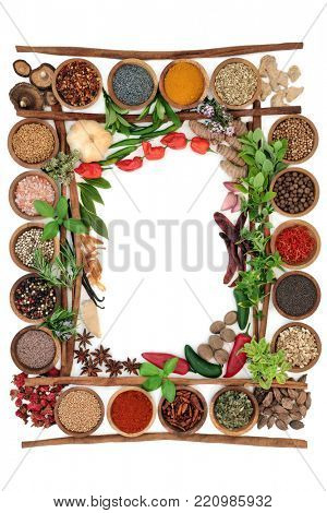 Abstract herb and spice border with fresh and dried herbs and spices with cinnamon sticks creating a frame  On white background, top view.