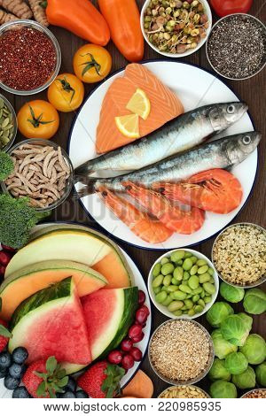 Healthy diet food concept with a selection of fresh seafood, fruit, vegetables, seeds and grains with super foods high in omega 3, vitamins, minerals, anthocyanins, antioxidants and fiber. Top view.